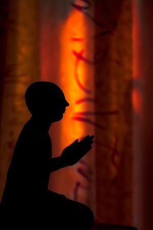 Zen Buddhism. Spiritual silhouette of Thai buddhist monk statue. Conceptual graphic sunset light image of holy man praying. Midnight sun oriental feel to this dark seeker of enlightenment.