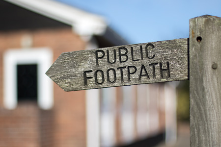 Public footpath sign. Right of way access through or adjacent to private residential property. Pedestrian legal right of passage via privately owned land. Selective focus.