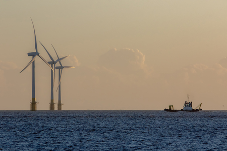 Offshore wind farm turbines on the horizon with passing ship. Green energy production and environmental conservation from sustainable resource. Beautiful tranquil image of massive turbines on the East coast of England.