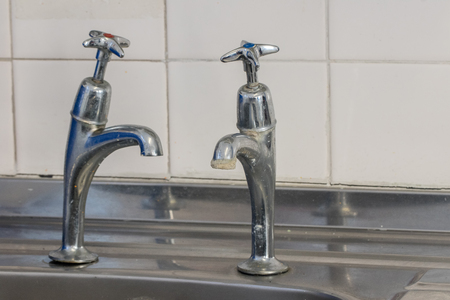 Bad plumbing. Limescale on old chrome tap. Selective focus on cold tap. Badly fitted kitchen faucet over stainless steel sink. Job for a plumber. Фото со стока - 114287557