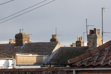 Northern town tiled roof tops with chimneys and aerials UK. Cramped urban working class housing. Old town building rooves.