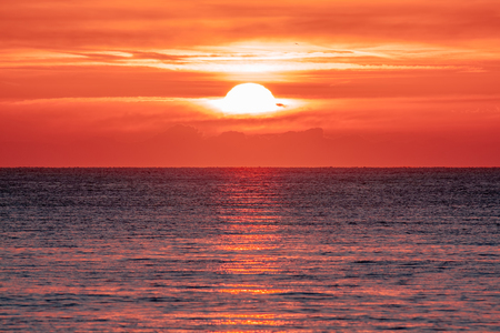 Sunrise over the ocean. Beautiful seascape. Orange sky reflecting on water at dawn. Spiritual new day dawning natural world background image. 版權商用圖片