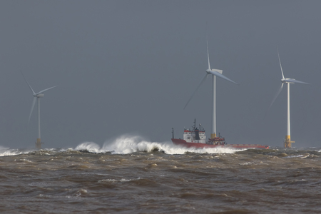 Ship sailing in rough sea. High cost energy of offshore wind farm turbines. Supply vessel battling ocean swell. Dangerous waves for shipping in storm conditions. Grey sky background with copy space Stok Fotoğraf