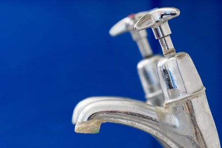 Limescale. Chrome faucet with hard water calcification deposit close-up. Tap needing decalcification and water softener. Scale build-up on old kitchen or bathroom plumbing. Blue background copy space.