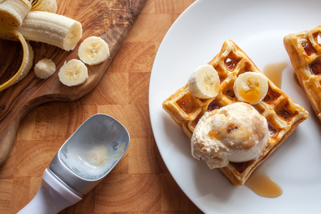 Banana waffles dessert with ice cream and maple syrup close-up. Flat lay close up image of sweet breakfast food with fruit ingredient. Home-made meal on white plate. Standard-Bild - 123443489
