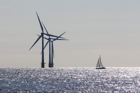 Wind power. Environmentally friendly sailing yacht. Offshore windfarm turbines. Tranquil scene of renewable resource power and travel with low carbon footprint lifestyle. Ecology landscape. 版權商用圖片