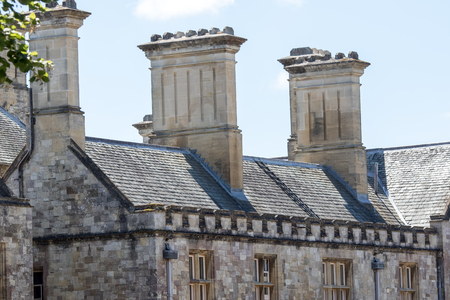 Rooftop stacks on medieval building. Close-up of historic roof detail. Imposing grand period house with slate roof tiles.