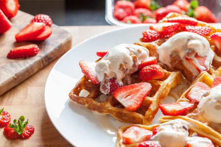 Strawberry waffles. Sweet dessert preparation. Serving with home-made ice cream. Delicious mouth-watering food on white plate. Naughty but nice meal close-up with organic fruit. Standard-Bild - 123443500