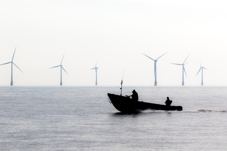 Offshore wind farm turbines. Border patrol security speed boat. Green energy demonstration at power plant location. Forces aided by coastguard patrolling the coast. Standard-Bild - 125979773