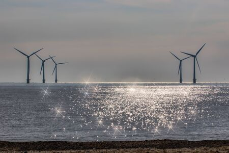 Divine light spiritual image. New age alternative lifestyle of green renewable energy. Offshore wind farm turbines silhouetted on the horizon. Beautiful seascape spiritual background image. Standard-Bild - 125979832