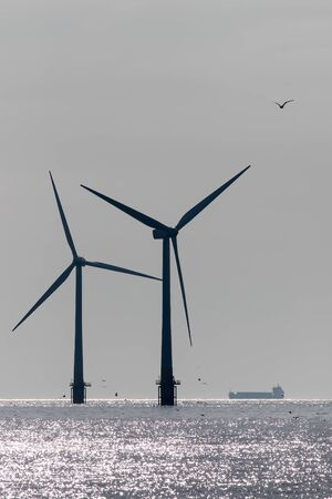 Clean energy production and development. Offshore wind power turbine silhouette with background supply vessel. Sustainable renewable resource image with maintenance ship supplying turbines at sea. Standard-Bild - 128084030