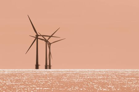 Global warming. Offshore wind farm turbines with twilight orange sky. Simple sparse and foreboding image representing the future of climate change. Natural eerie warm color with copy space. Standard-Bild - 128084026
