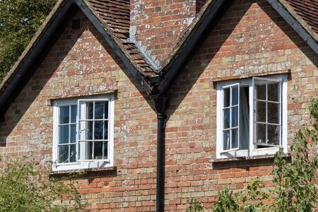 Open sash windows on a classic English country cottage house. Ventilation on a hot summers day for this beautiful old red brick building in the south of England. Standard-Bild - 128084046