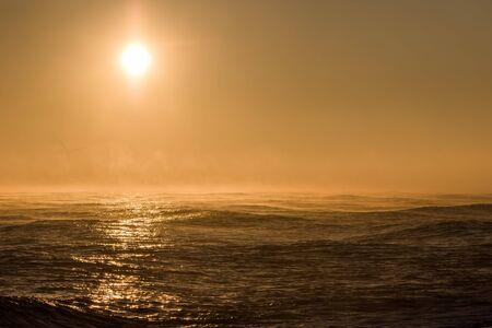 Seascape sunrise. Misty morning sun over sea with background wind turbine. Beautiful orange sky and light ocean waves with sunlight reflection. Spiritual landscape image. Banco de Imagens