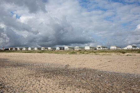 Holday beach homes. Static caravans along the UK coast. Line of coastal properties under uncertain mixed weather cloudy sky. English vacation resort. Standard-Bild - 128084080