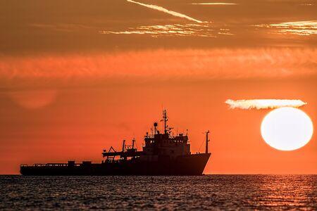 Tropical dawn at sea. Ship at sunrise on the ocean horizon. Orange glowing sky of a hot day. Standard-Bild - 128084083