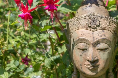Serene Buddha face. Garden statue with fuschia flowers. Buddhism at one with nature. Natural world image of traditional Zen Buddhist head with wildflowers and lush green foliage background. Stock Photo