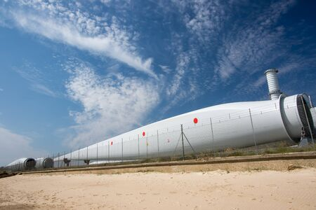Wind turbine blade parts. Renewable energy investment. Power industry development. Massive blades stored at Great Yarmouth outer harbour UK ready for offshore farm assembly and construction. Standard-Bild - 128084162