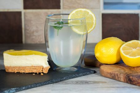 Lemon cheesecake. Authentic freshly prepared home-made organic lemonade. Summer food. Cool glass of thirst quencing drink prepared with lemons water and mint.