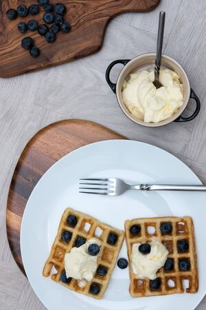 Delicious sweet blueberry waffle meal. Dessert food flat lay image. Organic blueberries and fresh low fat cream served on waffles as a simple fruit healthy breakfast.