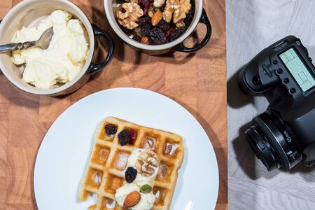 Flat lay food photography. Table top breakfast meal with camera. Preparation for a studio photo shoot. Waffle with fruit nuts and fresh low fat cream. Standard-Bild - 128084183
