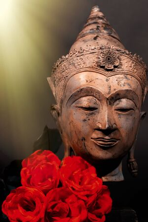 Unconditional love. Spiritual enlightenment. Traditional Buddha head and red roses with divine light. Spirituality and mindfulness. Deep Buddhist meditation. Religious contemplation of God and heaven. Standard-Bild - 128084185