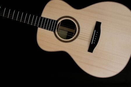 Acoustic guitar music close-up flat-lay image on black background. Singer songwriter folk guitarist musical instrument. Quality steel string grand concert. Solid spruce wood top. Ebony fingerboard.