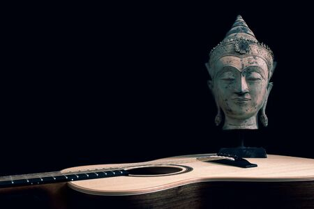 Spiritual music. Philosopher musician. The guitar songwriter muse. Traditional Buddhist statue on black background with copy-space. Buddha face with expression of calm meditation. Relaxing folk song. Standard-Bild - 128084200