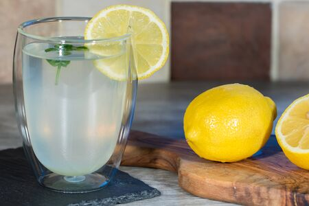 Lemon drink. Authentic home-made lemonade. Cool refreshing summer beverage. Glass with freshly squeezed juice, whole organic lemon and fresh mint. Food preparation. Фото со стока