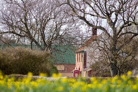 Rural England country scene. Trees, pub, red telephone box, and green roofed barn. Countryside village lifestyle background image.
