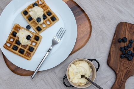 Delicious sweet blueberry waffle meal. Prepared dessert food flat lay image. Organic blueberries and fresh low fat cream served on waffles as a simple fruit healthy breakfast. Фото со стока