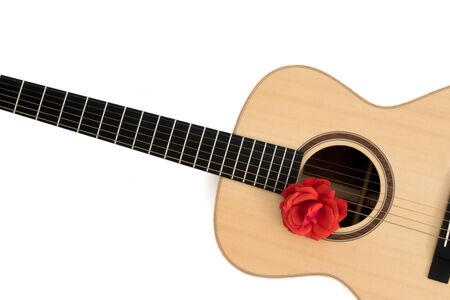 Love song. Acoustic guitar with red rose. Romantic music concept image. Folk guitar with flower on white background copy-space. Romance and serenade.