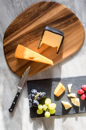 Delicatessen cheese-board cheese and grapes selection lunch. Rustic comfort food flatlay image. Red, white and black organic grapes with red and white hard cheeses served on grey woodgrain kitchen table.  Фото со стока