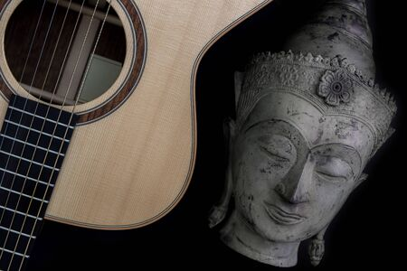 Spiritual music. Traditional meditating buddha statue with acoustic folk guitar. Representing music therapy, religious music and healing the mind. Chill-out new age music isolated on black background. Stock Photo