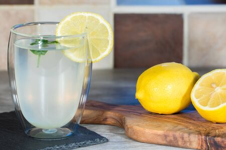 Home made lemonade. Refreshing healthy glass of cold water with lemon. Fresh lemons and mint with authentic summer drink. Simple five a day goodness.