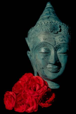 Spiritual love and enlightenment. Beautiful traditional blue buddha head statue with deep red rose flowers against black background. Aesthetic modern buddhism and nature image.