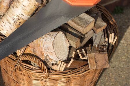 Firewood. Preparing for Winter. Assortment of sawn logs and old wood fuel with saw. Basket of cut wood ready to burn for heat.