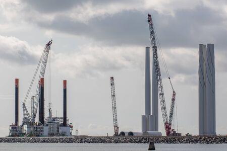 Inwestycja w energię odnawialną. Budowa i rozwój turbin wiatrowych na morzu. Części wieży farmy wiatrowej gotowe do transportu w zewnętrznym porcie Great Yarmouth Norfolk, Wielka Brytania Zdjęcie Seryjne