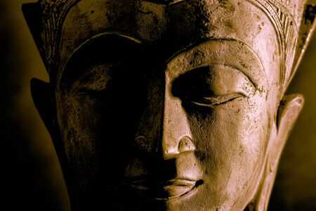 Buddhism. High contrast Buddha face close-up with dramatic side light. Metallic stone statue with calm mindful expression of closed eyes during meditation. Buddhist image of spiritual enlightenment. Banco de Imagens