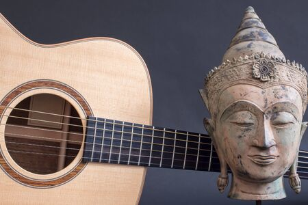 Buddha Guitar. The creative mind. Relaxing spiritual acoustic music. Transcendental sound for meditation. Traditional Buddhist statue head in meditational trance.  Pure creativity and spirituality.