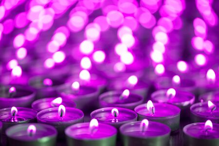 Purple pink candle light. Christmas or Diwali celebration tealight candlelight. Lit candles at night vigil. Close-up selective focus image of beautiful night light flames with blurred background. Фото со стока
