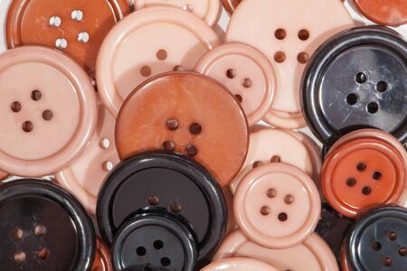 Plastic Buttons close-up. Childrens creative art and craft play background image. Simple brown cream pink and black painted discs for kids creativity.