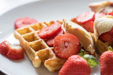 Strawberry waffles. Selective focus closeup of red fruit on authentic homemade sweet pancake waffle. Serving with icecream served on a white plate background. Фото со стока