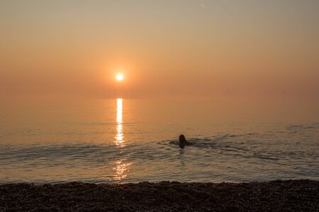 Alternative energy. Healthy lifestyle of a lone sea swimmer. Man or woman swimming by offshore wind farm turbines on a beautiful misty morning at sunrise. Perfect illustration of alternative lifestyle
