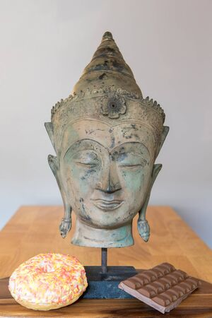Comfort food. Mental health and wellbeing with spiritual Buddha statue, sweet doughnut and chocolate. Representing mind over desire. Self control in the face of temptation. Banco de Imagens