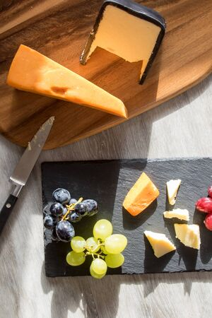 Red and white cheese flat lay food image with grapes on rustic kitchen table. Served on wood board and slate coaster with cheese knife. Banco de Imagens
