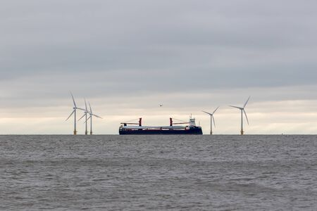 Wind turbine parts. Clean energy investment. Ship transporting blades via Scroby sands offshore wind farm Norfolk UK, a renewable green energy investment. Power industry manufacture and construction