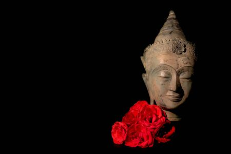 Peace and love. Serene traditional Buddha head statue with deep red roses. Finding spiritual enlightenment via meditation. Zen Buddhism purity and mindfulness. Black background with copy-space.