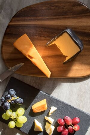 Cheese selection with red white and black grapes. Flatlay snack food image. Leicester and cheddar hard cheeses with fruit served on wood and slate coasters with knife flat lay food photography. Banco de Imagens