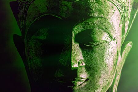 Spiritual enlightenment. Green buddha face statue close-up. Bold graphic image with atmosperic green tone light and star highlight. Religious lifestyle awakening via meditation. Serene power.